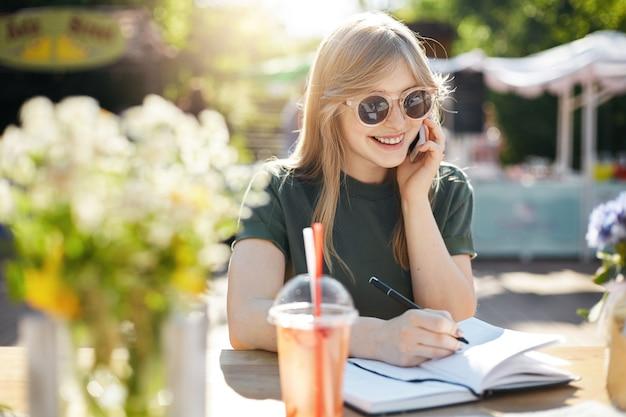 Ritratto di una giovane donna di affari o studente che scrive i suoi piani nel blocco note parlando su uno smartphone sorridente con gli occhiali