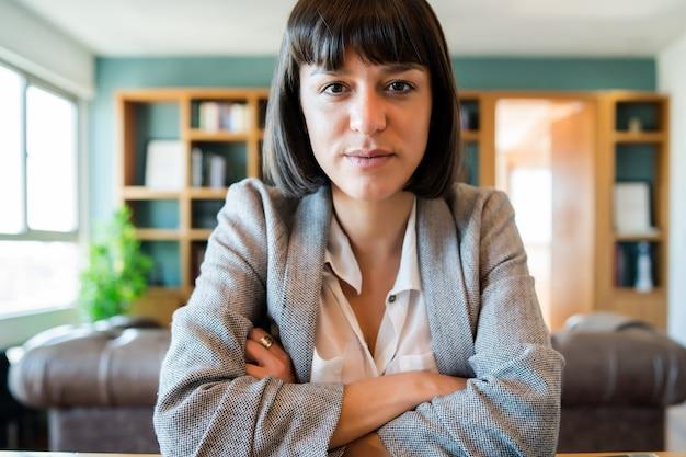 Ritratto di giovane donna d'affari in videochiamata da casa.