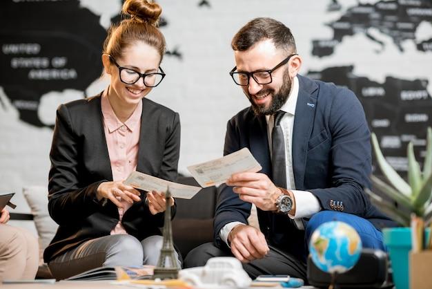 Ritratto di una giovane coppia di affari seduta presso l'ufficio dell'agenzia di viaggi con una bellissima mappa del mondo sullo sfondo