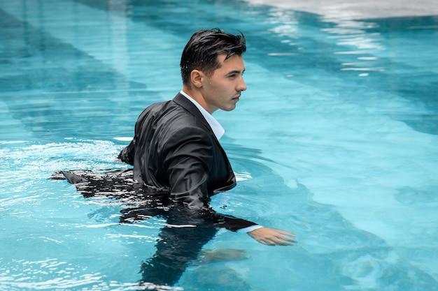 Ritratto di un giovane uomo d'affari che esce dall'acqua con una valigetta in una piscina
