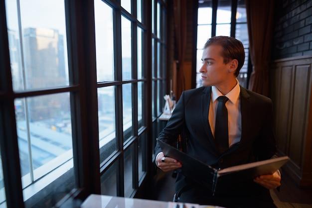 Ritratto di giovane imprenditore tenendo il menu e guardando fuori dalla finestra