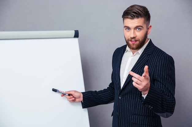 Ritratto di un giovane uomo d'affari in vestito che presenta qualcosa sul bordo bianco sopra il muro grigio