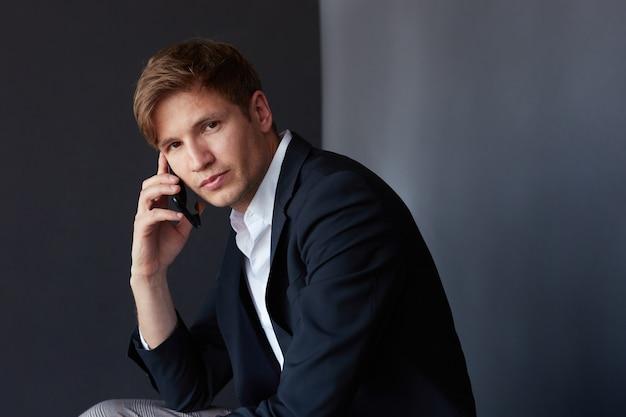 Ritratto di un giovane uomo d'affari in tuta seduto e guardando la fotocamera, tenendo il telefono vicino all'orecchio, sfondo nero.
