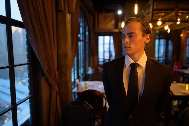 Ritratto di giovane uomo d'affari che indossa tuta al ristorante