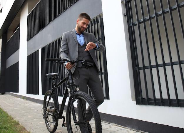 Ritratto di giovane uomo d'affari con la sua bicicletta guardando l'orologio
