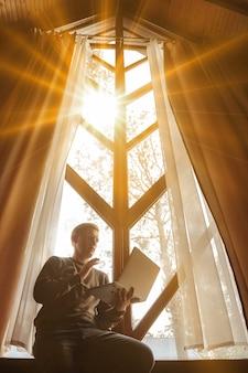Ritratto di giovane uomo d'affari con il computer portatile alla finestra del soggiorno in casa di campagna. uomo maniaco del lavoro in abiti casual da casa che lavora in vacanza. ispirazione creativa e start-up. copia spazio