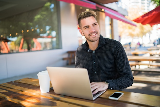 Ritratto di giovane uomo d'affari che lavora al suo computer portatile mentre era seduto in una caffetteria. tecnologia e concetto di business.