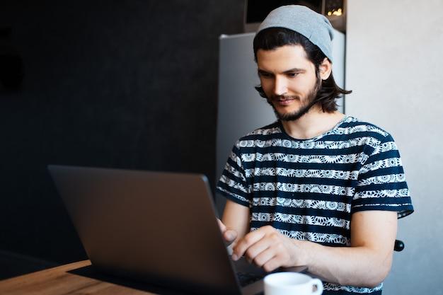 Ritratto di giovane uomo d'affari che lavora a casa sul computer portatile. indossa un cappello grigio.