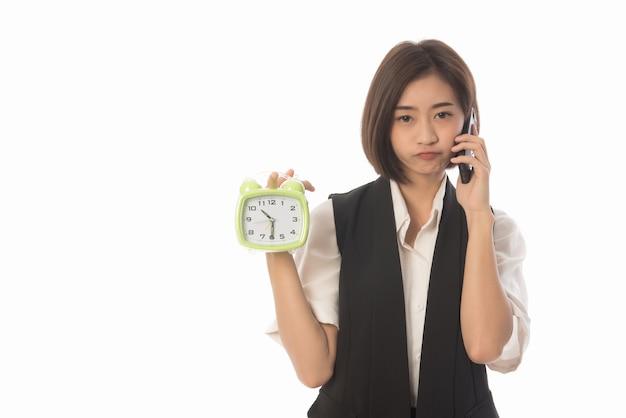 Ritratto di giovane imprenditrice tenendo l'orologio e chiamando il telefono isolato su bianco