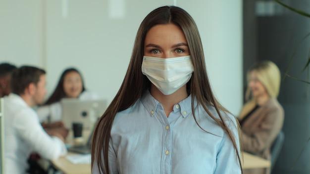 Ritratto di giovane donna d'affari in maschera medica donna responsabile delle vendite aziendali lavoratore in un ampio spazio aperto di coworking assistenza sanitaria nell'area di lavoro