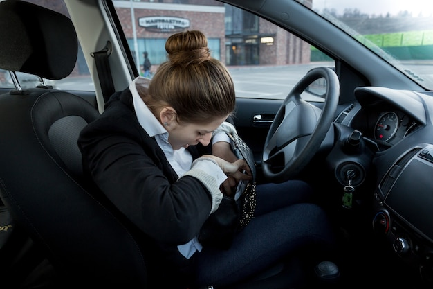 Ritratto di giovane imprenditrice seduta sul sedile del conducente e guardando dentro la borsetta