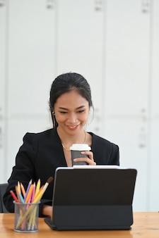 Ritratto di giovane imprenditrice seduto a lavorare con computer tablet e bere caffè caldo