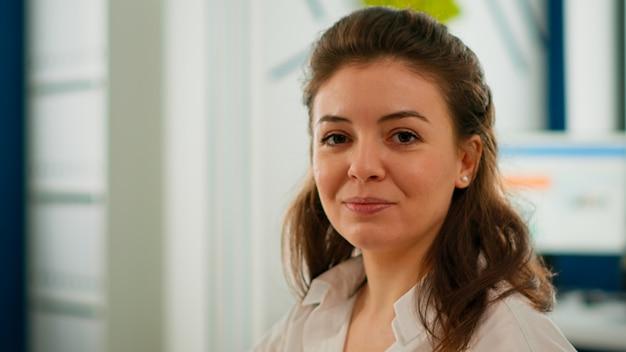 Ritratto di giovane donna d'affari che sorride alla macchina fotografica che si siede nella stanza di brainstorming, preparandosi per l'incontro con i partner. manager che lavora in attività finanziarie di avvio professionale pronto per la conferenza