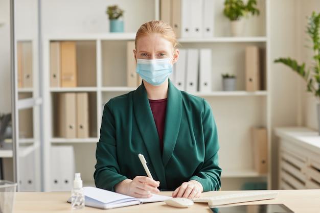Ritratto di giovane imprenditrice che indossa la maschera per il viso mentre si lavora alla scrivania in ufficio post pandemia