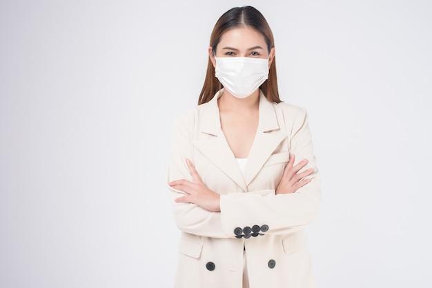 Ritratto di giovane donna d'affari che indossa una maschera chirurgica su sfondo bianco studio