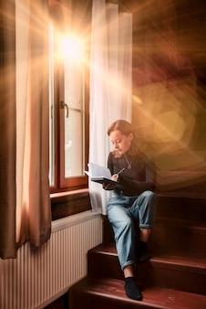 Ritratto di giovane imprenditrice con notebook e telefono alla finestra del soggiorno in casa di campagna. donna maniaca del lavoro in abiti casual domestici che lavorano in vacanza. ispirazione creativa e affari