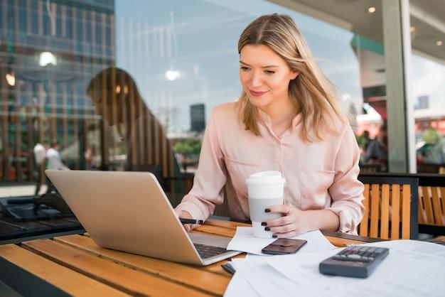 Ritratto di giovane imprenditrice lavorando sul suo computer portatile in una caffetteria. concetto di affari.