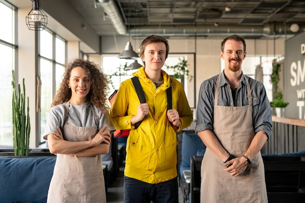 Ritratto di giovane cafe team composto da cameriere, cameriera e fattorino in piedi nella moderna caffetteria accogliente
