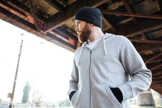 Ritratto di un giovane uomo barbuto casual con cappello in piedi sotto il ponte urbano e guardando lontano