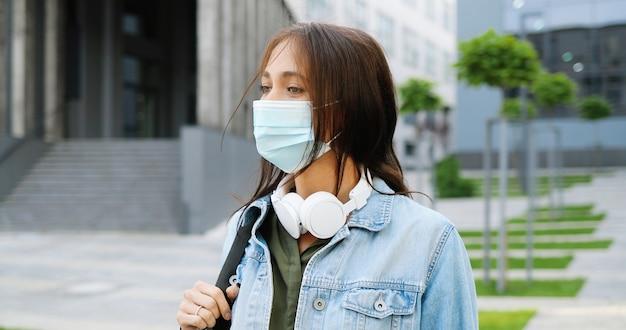 Ritratto di giovane bella donna caucasica nella mascherina medica che osserva alla macchina fotografica all'aperto e che ride. attraente studentessa allegra in cuffia e con la schiena in strada in quarantena. pandemia.