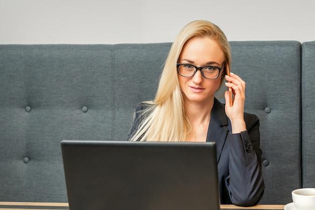 Ritratto di una giovane imprenditrice caucasica in bicchieri chiama su uno smartphone con un computer portatile al tavolo nella caffetteria