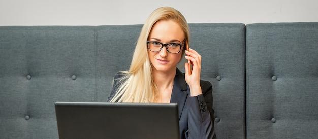 Ritratto di una giovane imprenditrice caucasica in bicchieri chiama su uno smartphone con un laptop al tavolo