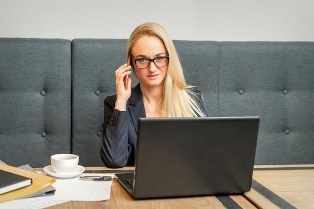 Ritratto di una giovane imprenditrice indoeuropea in bicchieri chiama su uno smartphone con un laptop in