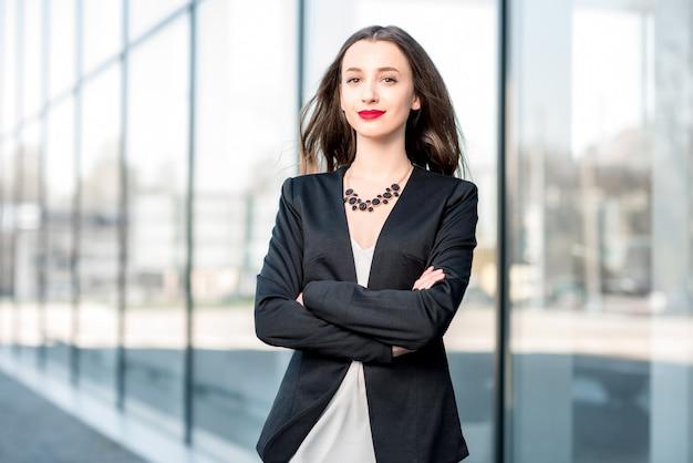Ritratto di una giovane donna d'affari caucasica in piedi all'aperto vicino alla facciata moderna
