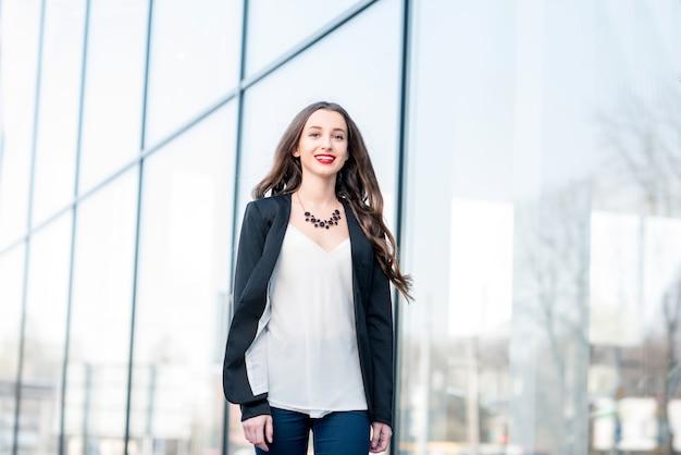 Ritratto di una giovane donna d'affari caucasica che cammina all'aperto vicino alla facciata moderna