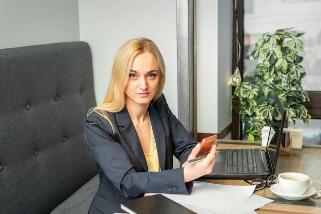 Ritratto di una giovane imprenditrice caucasica con uno smartphone e un laptop al tavolo guardando il