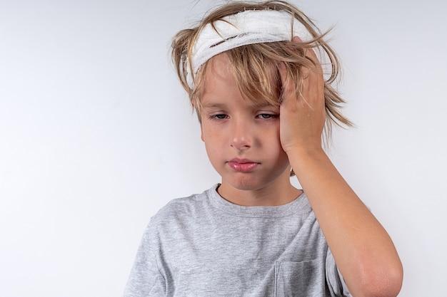 Ritratto di giovane indoeuropeo ragazzo carino capelli biondi con lesioni da trauma e benda testa isolato su sfondo bianco ragazzo tiene la testa con la mano
