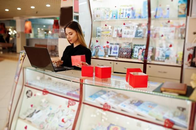 Ritratto di giovane donna femminile caucasica tenere confezioni regalo rosse. piccola impresa di negozio di souvenir di caramelle.