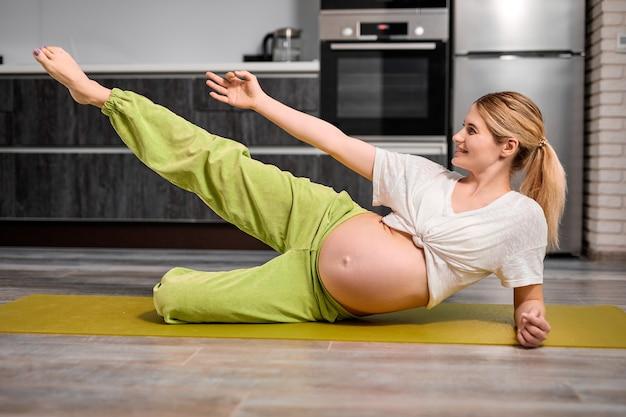 Ritratto di giovane donna incinta caucasica alzando la gamba facendo esercizi sul tappetino fitness