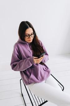Ritratto di giovane donna caucasica in occhiali utilizzando il telefono cellulare nella stanza vuota con pareti bianche.