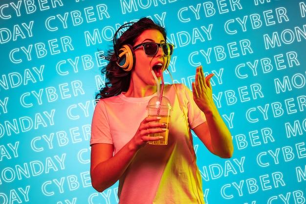 Ritratto di giovane donna caucasica in cuffie e occhiali da sole su sfondo blu con lettere al neon. concetto di vendite, venerdì nero, lunedì cibernetico, finanza, affari. negozi online e bolletta dei pagamenti.