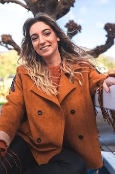 Ritratto di una giovane donna caucasica seduto su una panchina al centro di donostia-san sebastian; paesi baschi.
