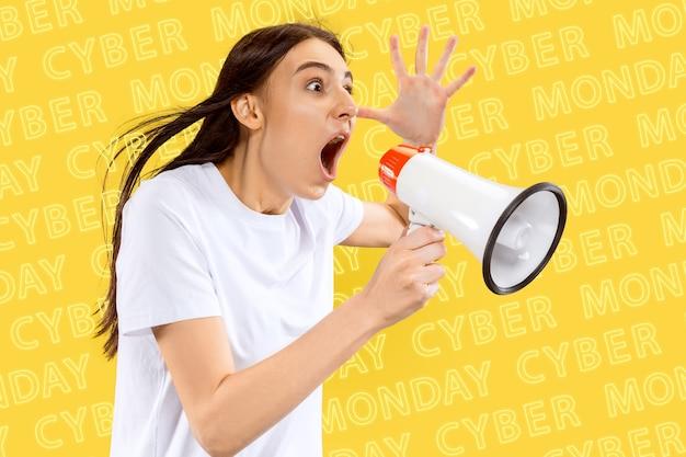 Ritratto di giovane donna caucasica su sfondo giallo con lettere al neon. chiamare con la bocca aperta. concetto di vendite, venerdì nero, lunedì cibernetico, finanza, affari. negozi online e bolletta dei pagamenti.