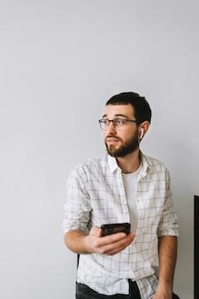 Ritratto di giovane uomo caucasico allegro in bicchieri e auricolari utilizzando il telefono cellulare.