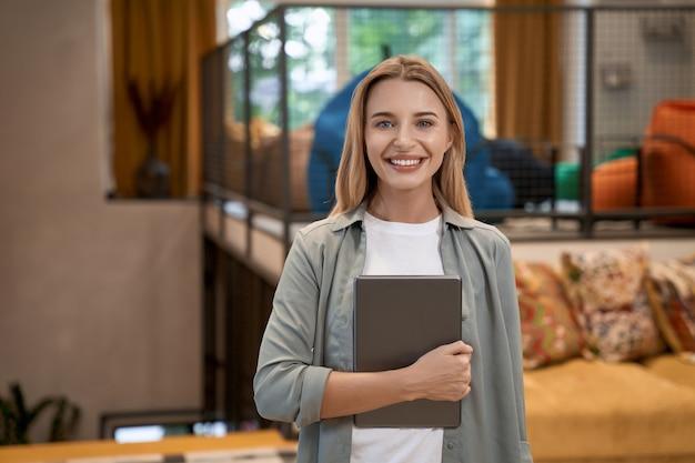 Ritratto di una giovane donna caucasica allegra impiegata d'ufficio in possesso di tablet digitale e