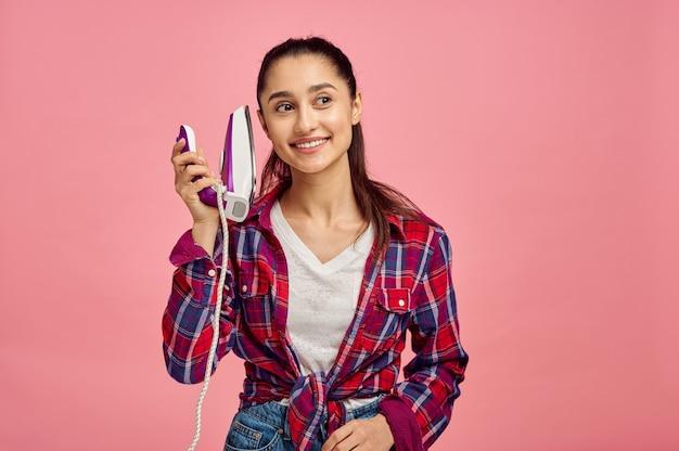Ritratto di giovane casalinga allegra con muro di ferro, rosa