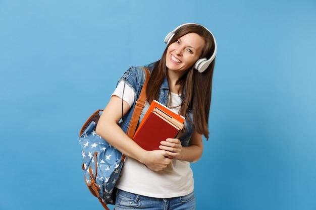 Ritratto di giovane studentessa allegra piacevole in vestiti di denim con musica d'ascolto delle cuffie dello zaino, tenere i libri di scuola isolati su fondo blu. istruzione al college universitario di scuola superiore.