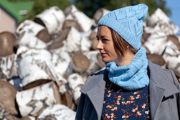 Ritratto di una giovane donna allegra in un cappello lavorato a maglia, giacca, bel vestito e stivali, sorrisi carini e si siede su tronchi di betulla. il concetto di stile rustico e vita nei tempi antichi