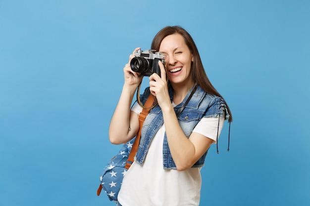 Ritratto di giovane studentessa allegra in abiti in denim con zaino per scattare foto su retro macchina fotografica vintage isolata su sfondo blu. istruzione all'università. copia spazio per la pubblicità.