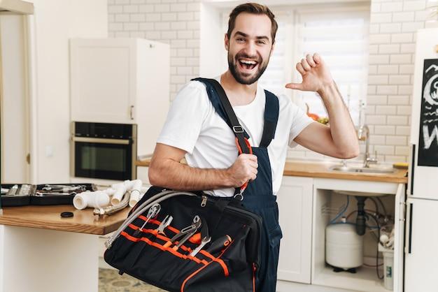 Il ritratto di giovane idraulico positivo allegro dell'uomo lavora in uniforme all'interno che tiene la borsa con l'attrezzatura che indica a se stesso.
