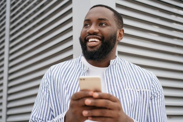 Ritratto di giovane uomo d'affari africano fiducioso che tiene il cellulare, comunicazione, lavoro in linea, in piedi sulla strada