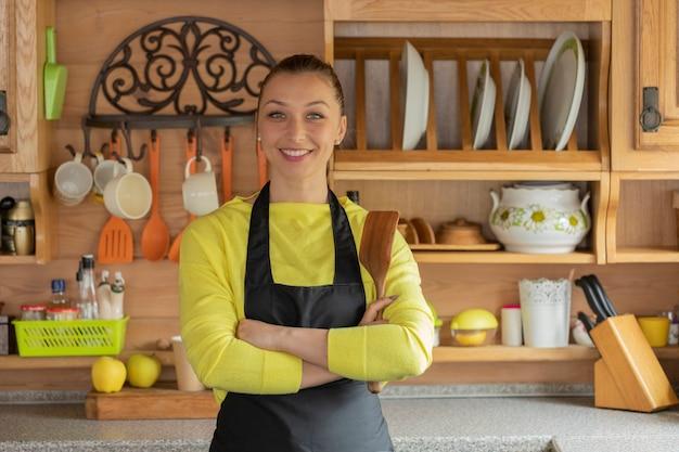 Ritratto di giovane casalinga fiduciosa in grembiule nero in piedi con una spatola di legno nelle mani