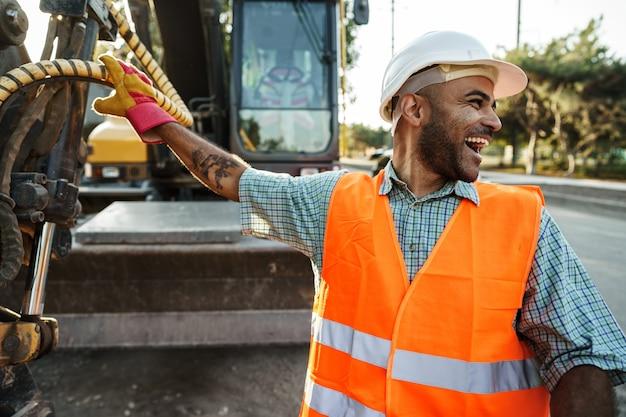 Ritratto di giovane ingegnere edile che indossa elmetto protettivo