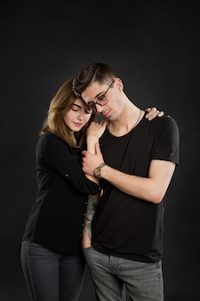 Ritratto di giovane coppia in abiti neri con gli occhiali alla moda e in posa su sfondo nero.