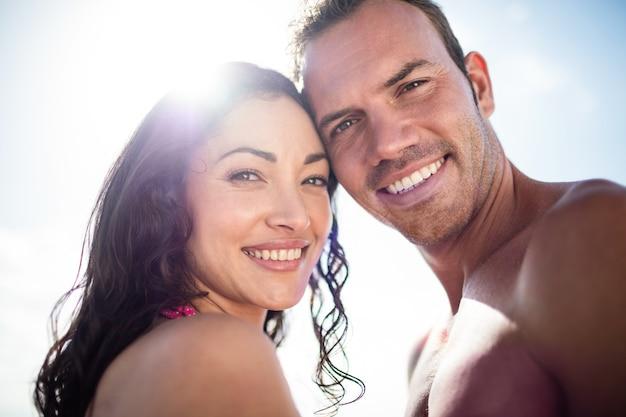 Ritratto di giovane coppia che si abbracciano sulla spiaggia