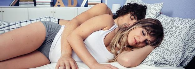 Ritratto di giovane coppia innamorata che si rilassa insieme sdraiata su un letto. amore e concetto di relazioni di coppia.
